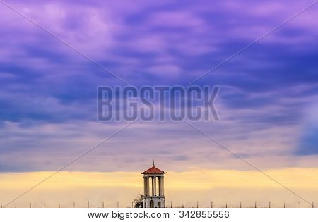 Magnificent Sunset With Dramatic Thunderclouds. In The Foreground Is A Tower.sunset Over Water Magni