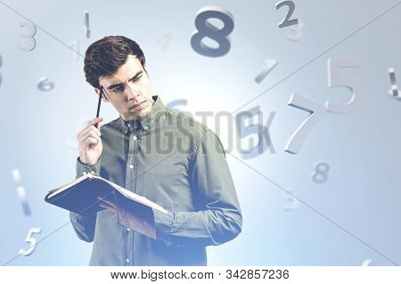 Pensive Young Man With Notebook Standing Over Gray Background With Falling Numbers. Concept Of Maths