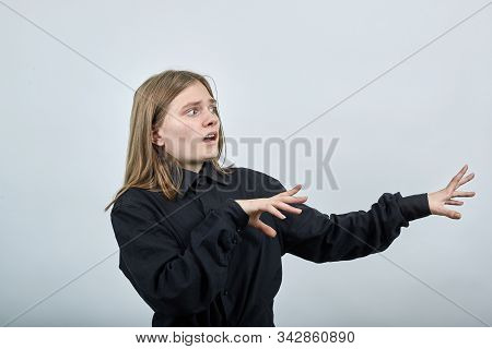 Disappointed Young Woman In Fashion Black Shirt Isolated On Gray Background In Studio Spreads Hands