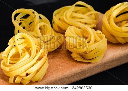Pasta Alluovo, Tagliatelle Pasta, Round Balls Of Raw Pasta On The Wooden Cutting Board On Black Back