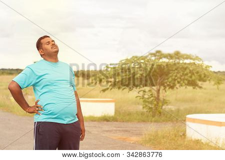 Tired Young Obese Man Holiding His Back While Jogging - Concept Of Fat Man Fitness And Unhealthy Lif
