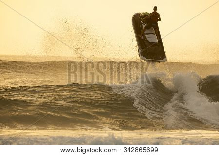 Silhouette Of Man Riding A Water Scooter And Jumping Over A Wave On Sunrise