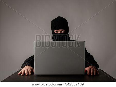 Hacker In Mask Using A Laptop.
