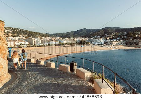 Tossa De Mar, Spain - August 2, 2019: Two Unknown Girls Go Down To The Sea From An Ancient Fortress