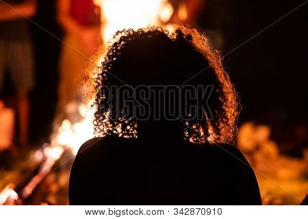 Silhouette Of A Curly Hair Woman Sitting In The Front Of The Fire, Seen From Behind During Dark Nigh