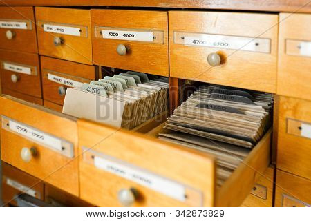 A File Cabinet Or Cabinet With An Open Drawer And Files. Database Concept. File Cabinet With Library