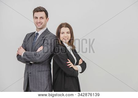 Business Man And Woman Standing Alongside, Looking At The Camera, Smiling, Their Hands Folded.