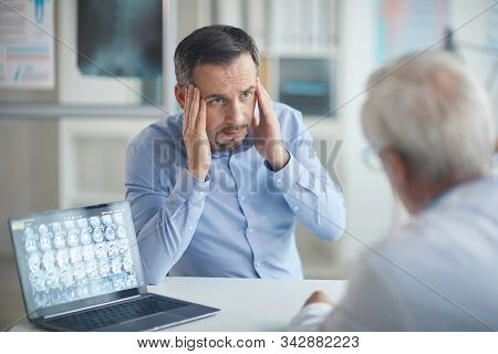 Mature Man Complaining O Headache To The Doctor While Sitting At The Table At Doctors Office
