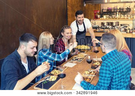 Happy Business Owner Serving Food To Smiling Group Of Young Friends In Small Family Tavern Restauran