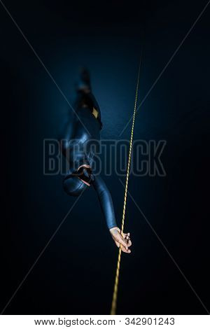 Woman freediver descends along the rope into the depth. Tilt shift effect applied