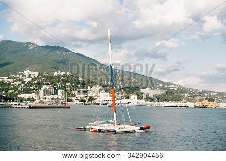 Yalta. Crimea. Russia - August 31, 2017: Port of Yalta in Crimea. Moored Trimaran on Foreground.