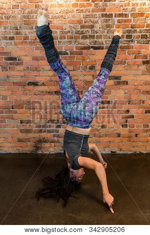 A Side Profile Full Body Shot Of An Upside Down Woman As She Performs A Difficult Twisting Splits He