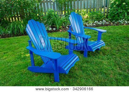 Blue Adirondack chairs in a back yard.