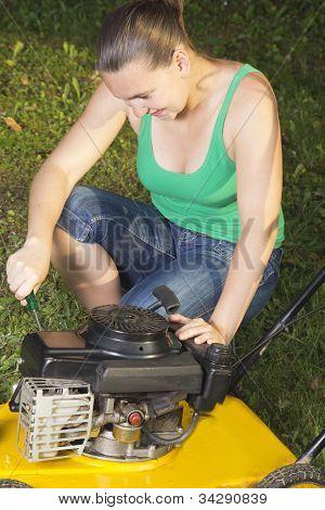 Cute girl repairing lawn mower