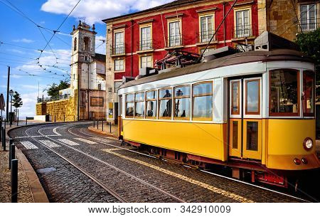 Lisbon Portugal. Yellow vintage tram driving by street of paving stones in district Alfama. Cityscape panorama with old houses and tower in sunny day with blue sky and white clouds.