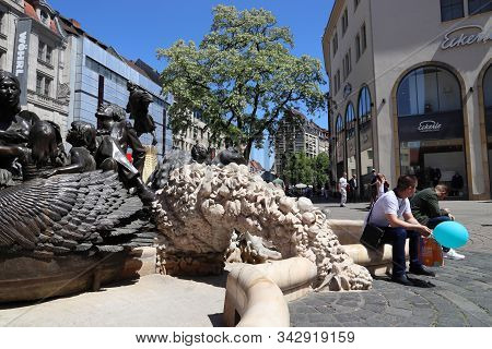 Nuremberg, Germany - May 8, 2018: People Visit Ehekarussell Controversial Fountain At Ludwigsplatz (