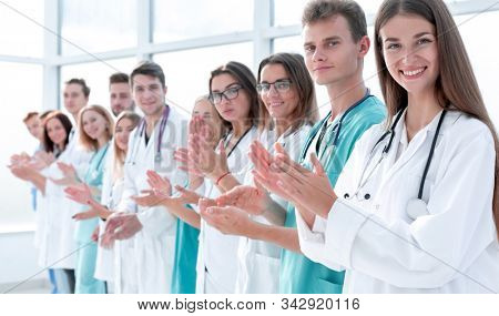 group of smiling young doctors applauds standing in a row