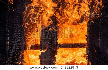 Dangerous Fire. Whole House And Yard On Fire. A Fire Destroys A Charred Burnt House. Charred In Flam