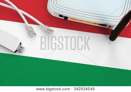 Hungary Flag Depicted On Table With Internet Rj45 Cable, Wireless Usb Wifi Adapter And Router. Inter