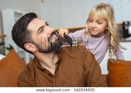 Adorable Little Girl Brushing Beard Of Her Smiling Father