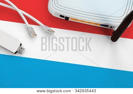 Luxembourg Flag Depicted On Table With Internet Rj45 Cable, Wireless Usb Wifi Adapter And Router. In