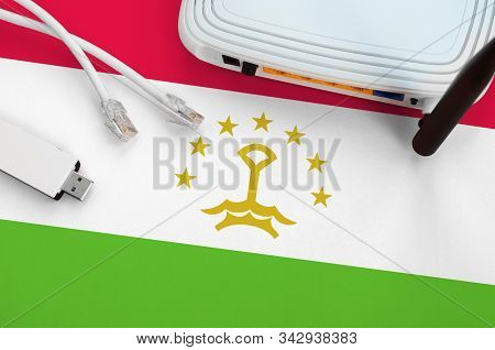Tajikistan Flag Depicted On Table With Internet Rj45 Cable, Wireless Usb Wifi Adapter And Router. In