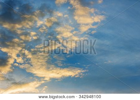 Golden Clouds On A Blue Sky At Sunset. Beautiful Nature Background. Wonderful Atmosphere Scenery In