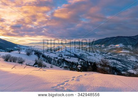 Mountainous Countryside In Winter At Sunrise. Snow Covered Hills And Fields Of Carpathian Rural Area
