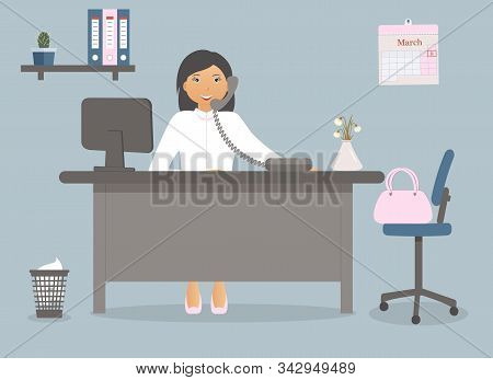 Cute Woman In The Office At The Table On International Women Day On March 8.vase Of Spring Flowers G