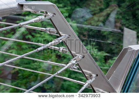 A Corner Of A Glass Bridge With Tension Steel Cables And A Cable Tensioner With Thread Over Green Tr
