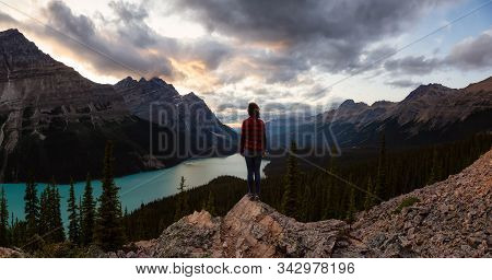 Adventurous Girl Standing On The Edge Of A Cliff Overlooking The Beautiful Canadian Rockies And Peyt