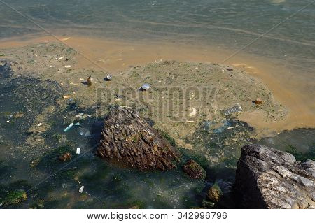 Rippling Sea Waves Surf Unhygienic Trash To Rocky Coastline Polluting Beach And Leading To Disaster