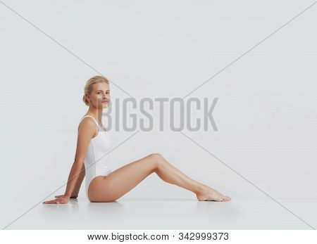 Young, Beautiful, Fit And Natural Blond Woman In White Swimsuit Applying Moisturizing Cream. Massage