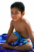 An handsome Indian kid having fun at a tropical beach poster