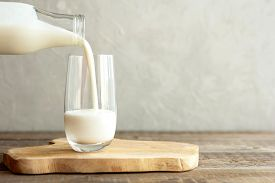 Kefir, Milk Or Turkish Ayran Drink Are Poured Into A Glass Cup From A Bottle. A Glass Stands On A Wo