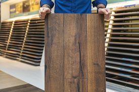 Flooring Store Salesman With Laminate Floor Sample Panel In Hands