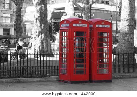 Two London Telephone Boxes Against A Black & White Background