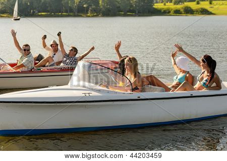 Waving young friends sitting in motorboats enjoying summertime