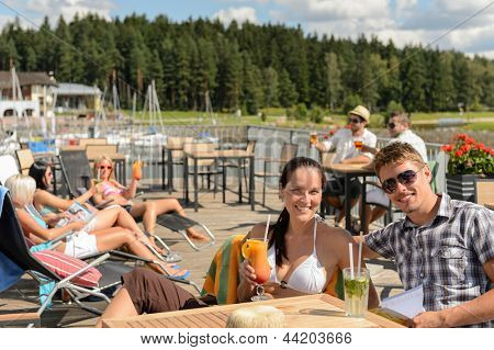 Young people enjoying summer vacation sunbathing drinking at beach bar