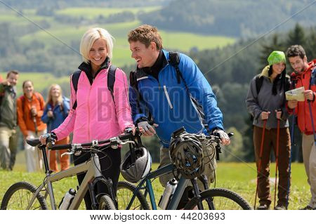 Cheerful cyclist couple with mountain bikes relaxing countryside
