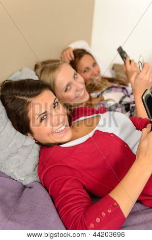 Three smiling young girl lying on bed using smart phones