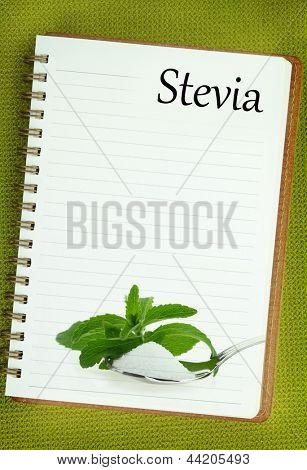 Fresh Stevia Rebaudiana and sugar on blank notebook page