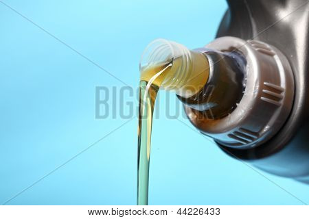 Can With Car Engine Oil Pouring Blue Background