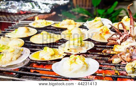 Grilled Scallops Topped With Butter, Garlic And Parsley On Flaming Grill.