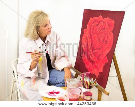 Artist Studies Her Painting Of A Rose