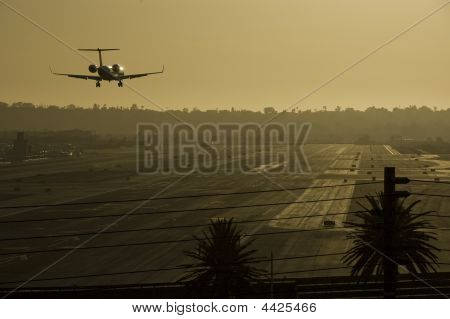 Airplane Landing On Runway During Sunset.