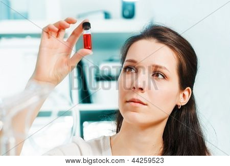 Laboratory assistant with a sample of blood in a test tube