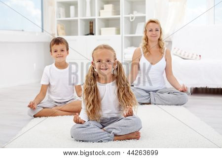 Kids doing yoga relaxing exercise with their mother at home