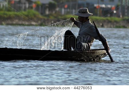 Vietnamese fisherman fishing in the Mekong delta, Vietnam