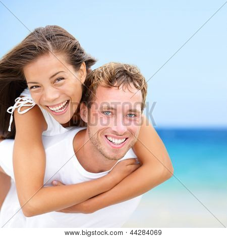 Happy couple on beach fun summer vacation. Multiracial Young newlywed couple piggybacking smiling joyful elated in happiness concept on tropical beach with blue water, sky. Asian woman, Caucasian man. poster
